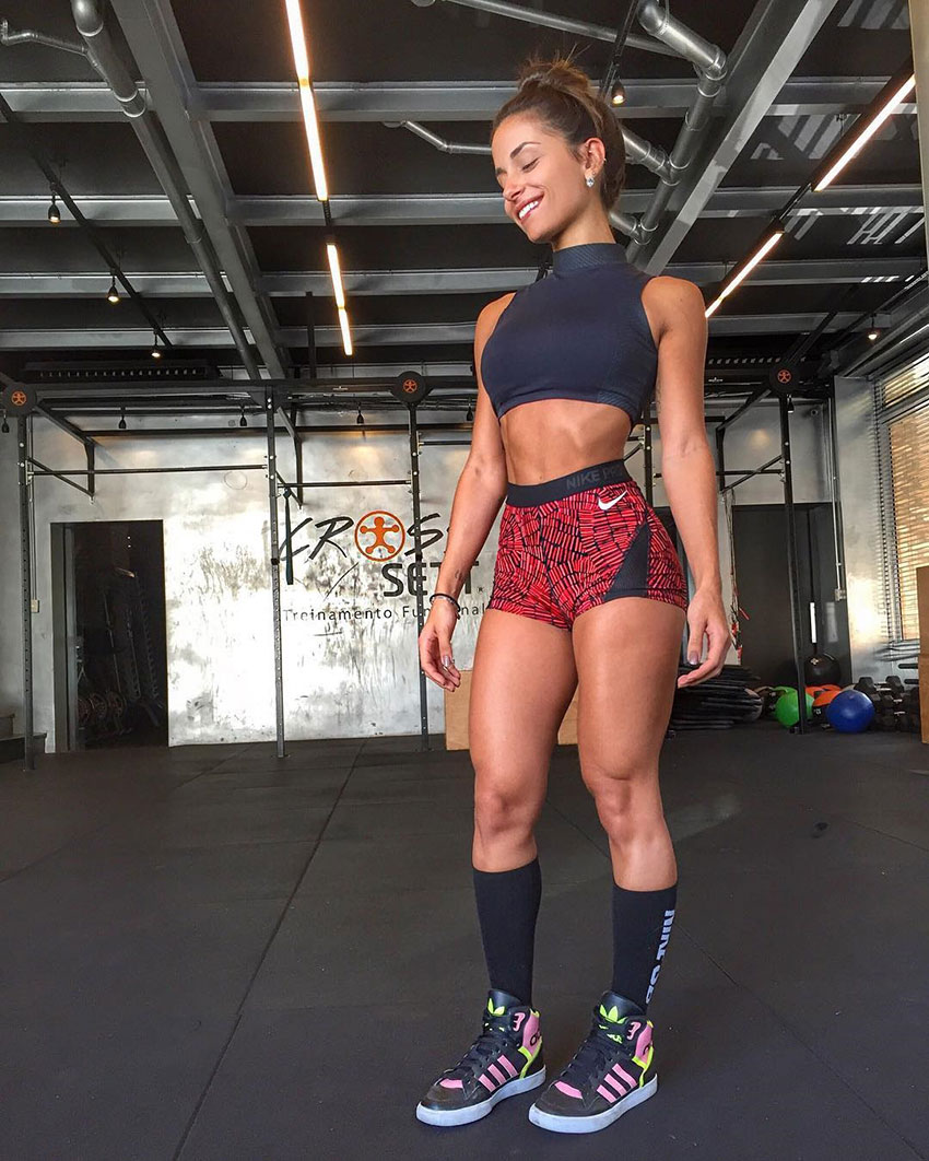 Thamires Hauch standing in the gym wearing tight gym clothes looking lean and healthy