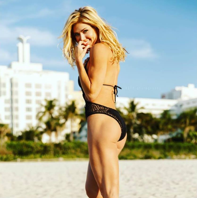 Torrie Wilson on the beach, looking and smiling at the camera