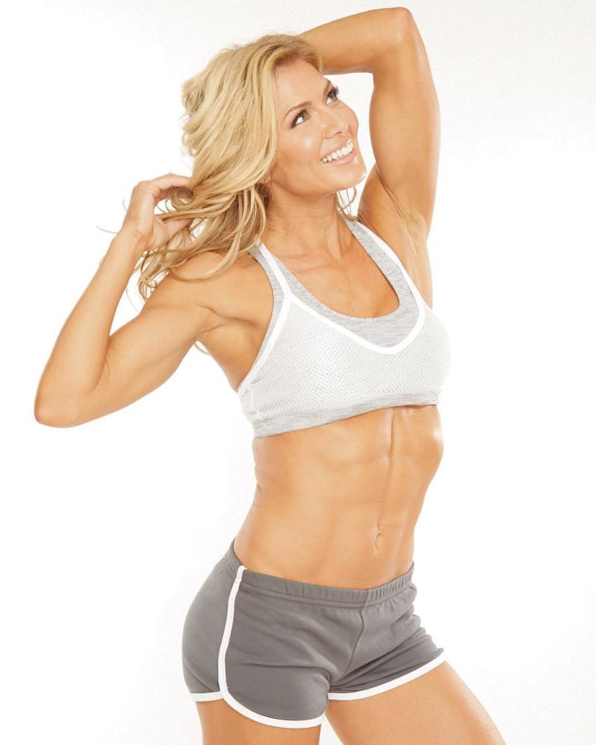 Torrie Wilson smiling as she looks up in the sky, wearing gym clothes, looking lean and fit