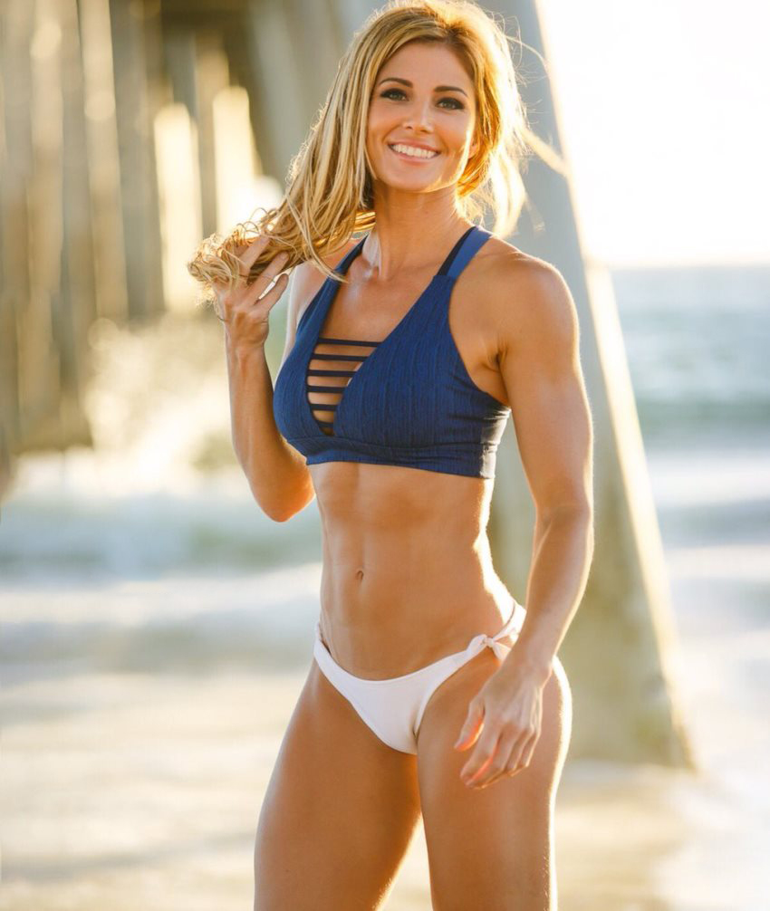 Torrie Wilson on the beach in a bikini, smiling at the camera, her abs, legs and arms looking awesome