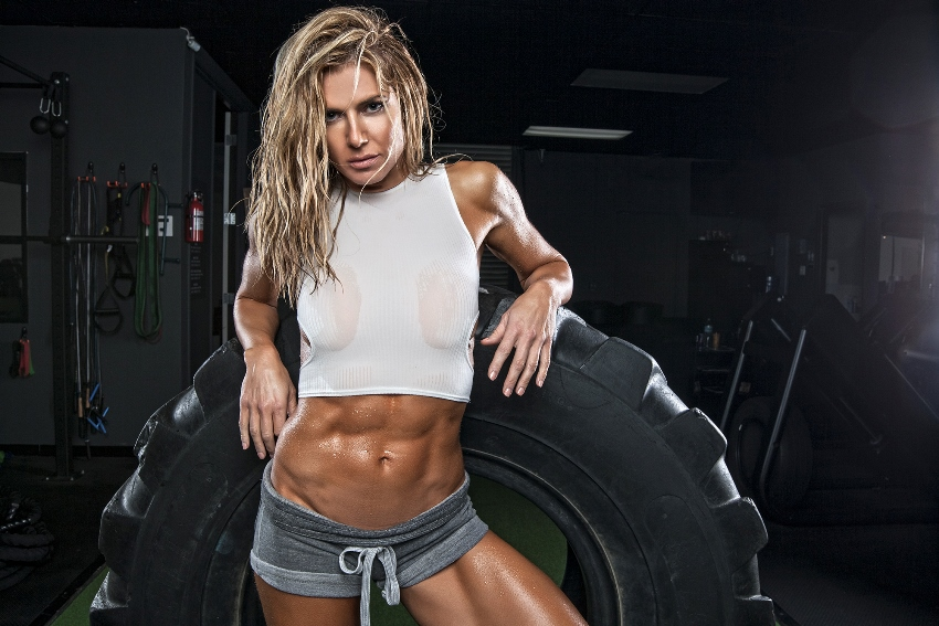 Torrie Wilson leaning against a big tire, flexing her ripped abs and legs