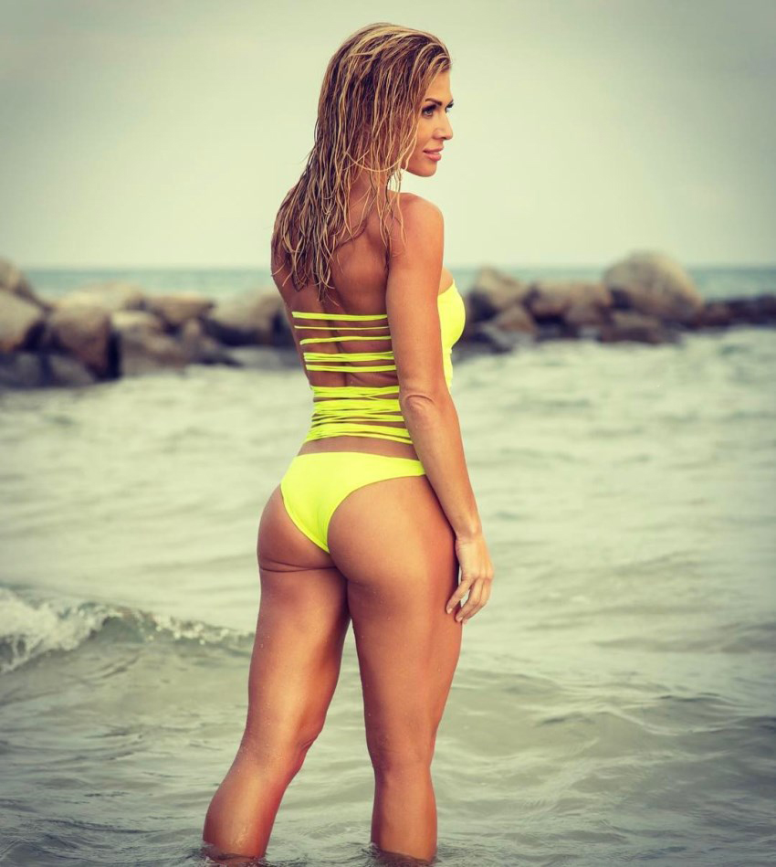 Torrie Wilson standing on the shore, showcasting her amazing glutes and legs