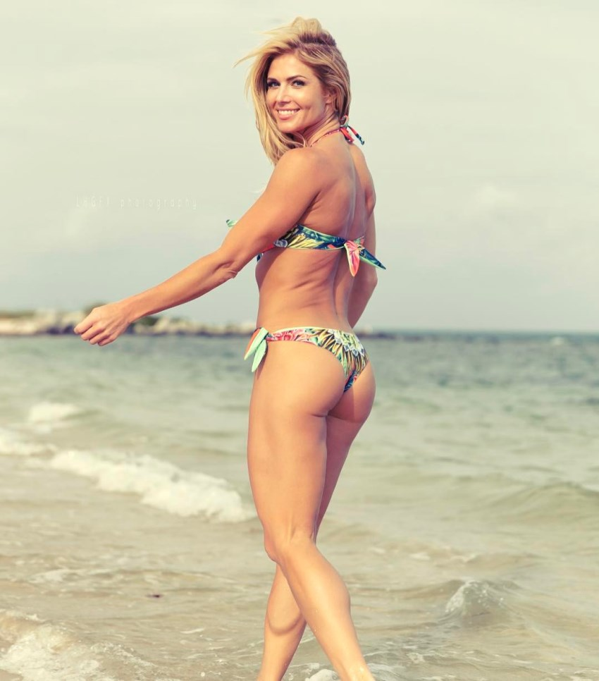 Torrie Wilson walking on the beach as she turns around and smiles at the camera, showing her awesome legs and glutes