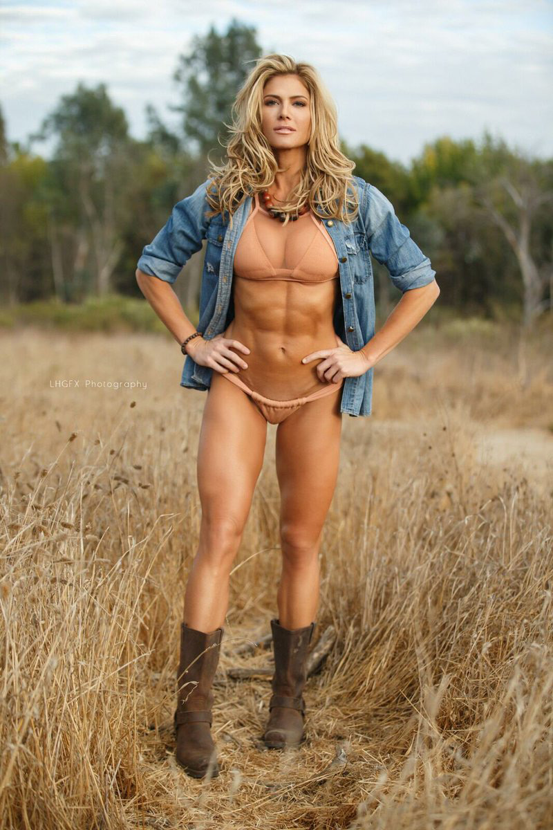 Torrie Wilson standing in a field posing with her bikini on looking ripped