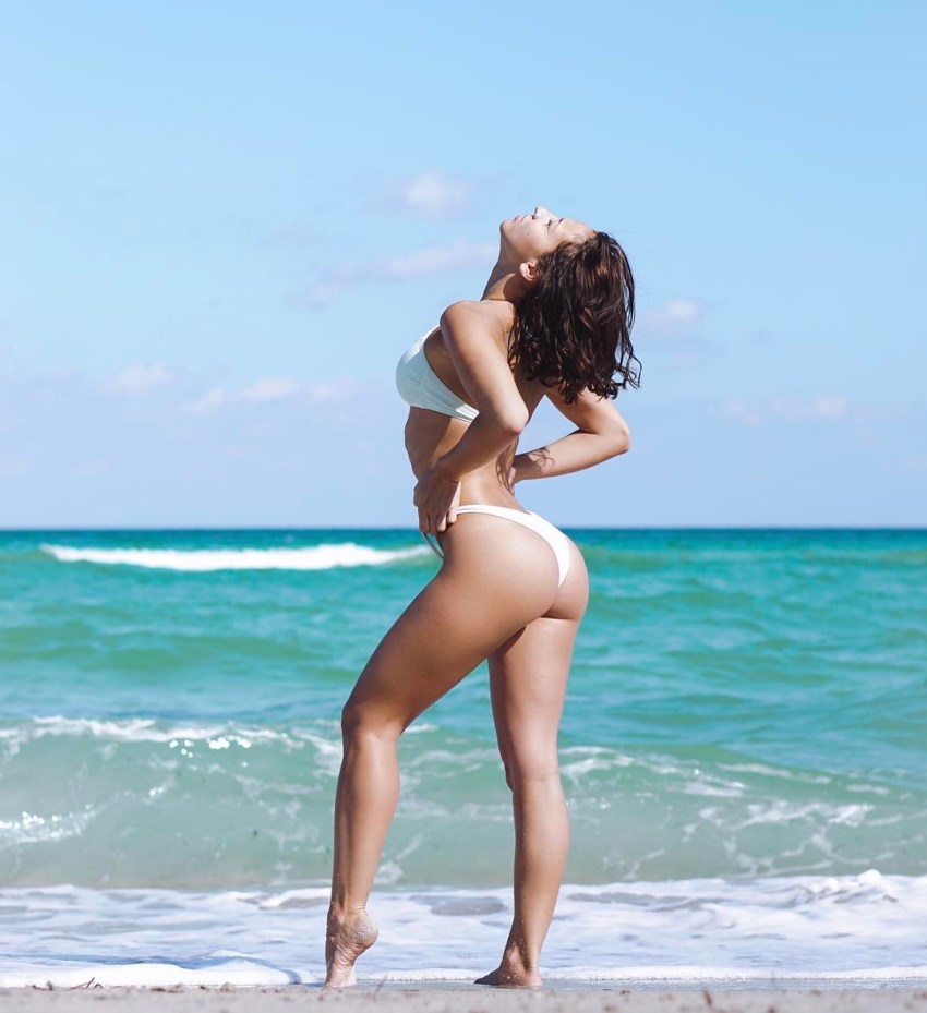 Vicky Justiz standing on the beach, her glutes and legs looking incredible
