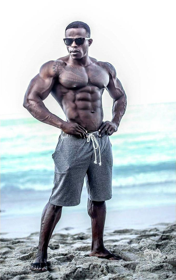 Andre Ferguson posing next to a beach with his short off looking ripped and muscular