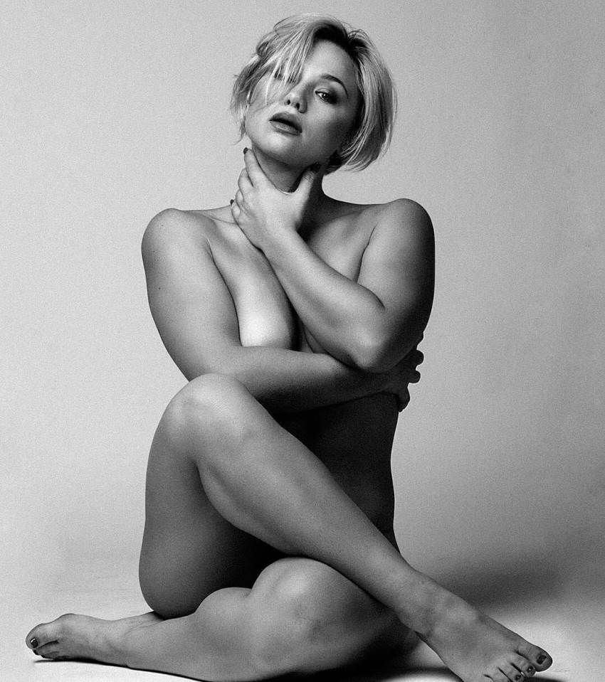 Anna Matthews posing naked for a photo shoot, sitting down in a pose covering her intimate areas, looking fit and curvy