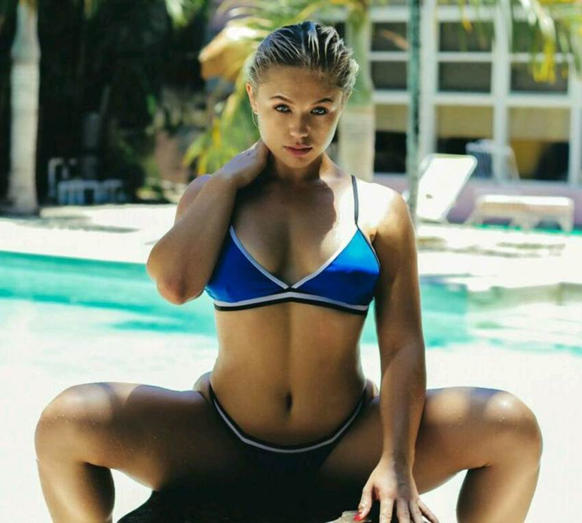Anna Matthews sitting by the pool in a blue bikini, looking curvy and lean