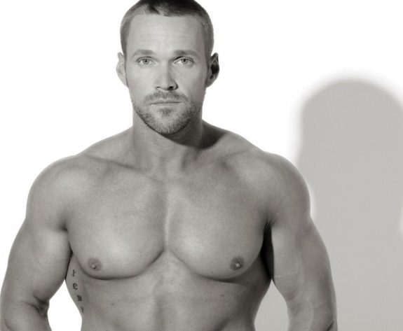 Chris Powell posing shirtless for a photo, looing lean and fit