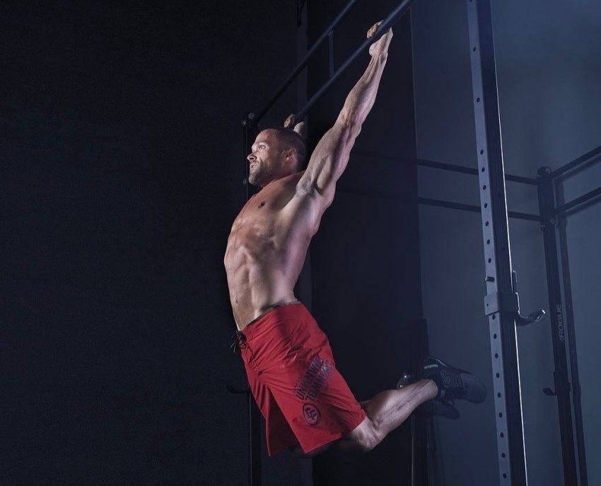 Chris Powell hanging on a bar, doing an exercise