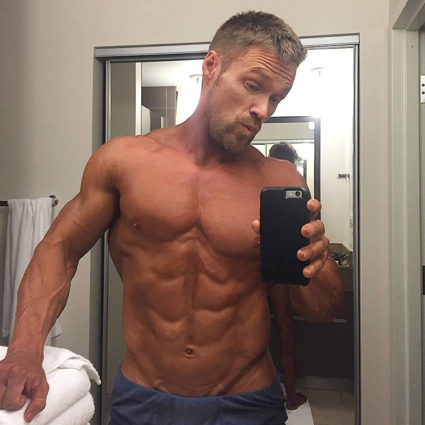 Chris Powell taking a bathroom selfie, his abs looking ripped