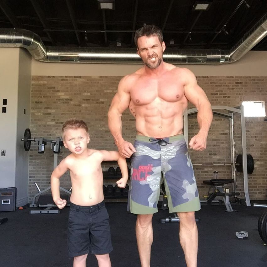 Chris Powell posing shirtless with his son, looking healthy and fit