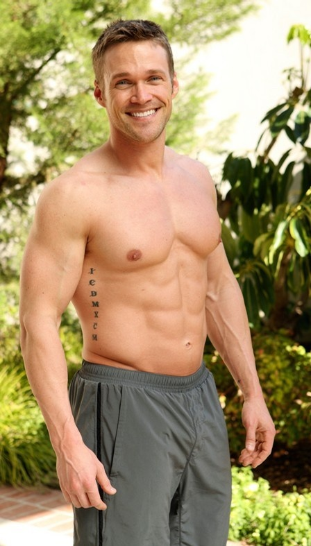 Chris Powell posing shirtless outdoors, looking lean and fit