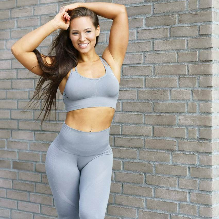Christina Fjaere posing at the photo and smiling, her abs and arms looking lean