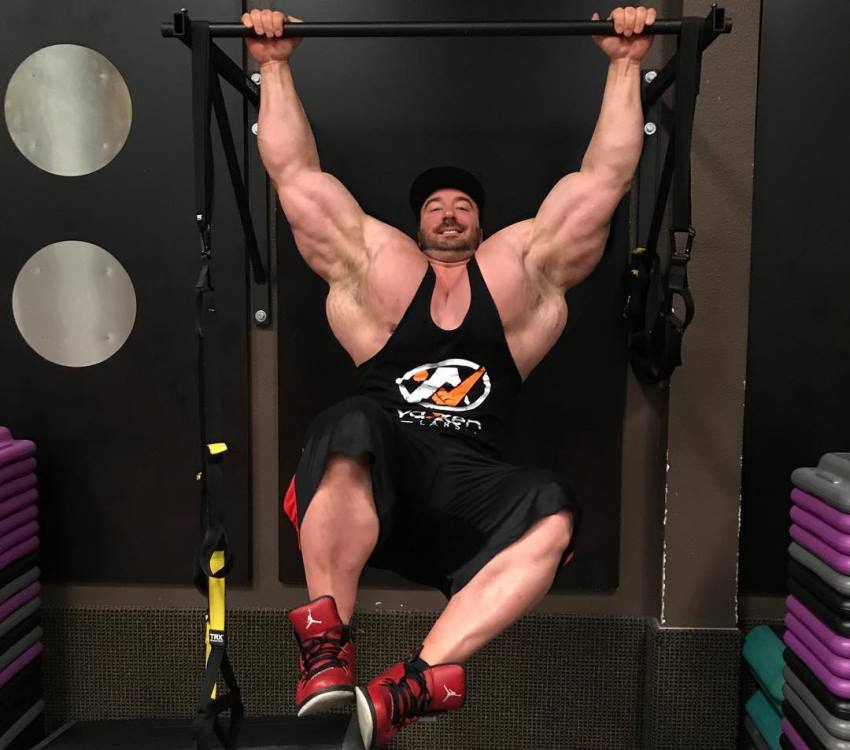 Craig Golias ganging on a bar in black tank top, his lats and arms looking enormous