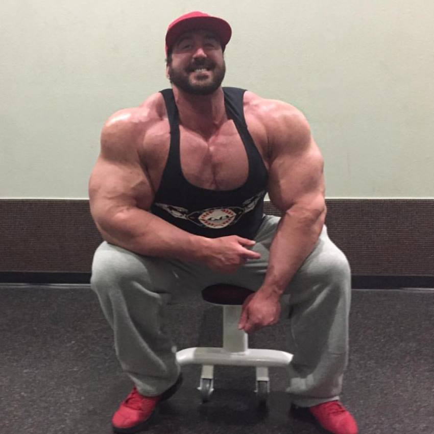 Craig Golias sitting on a bench posing for the camera and flexing his big arms