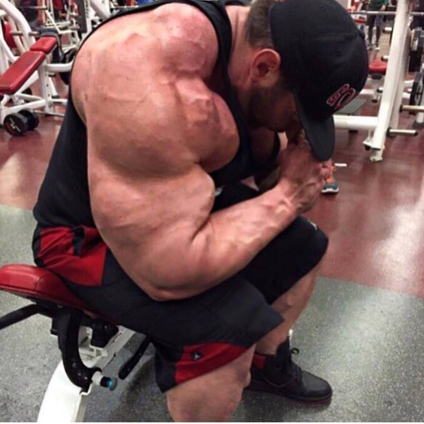 Craing Golias sitting on a bench in the gym, his arms and shoulder looking massive
