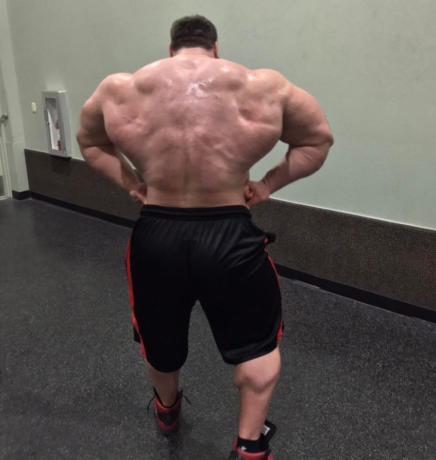 Craig Golias in a rear lat spread pose, looking massive and lean