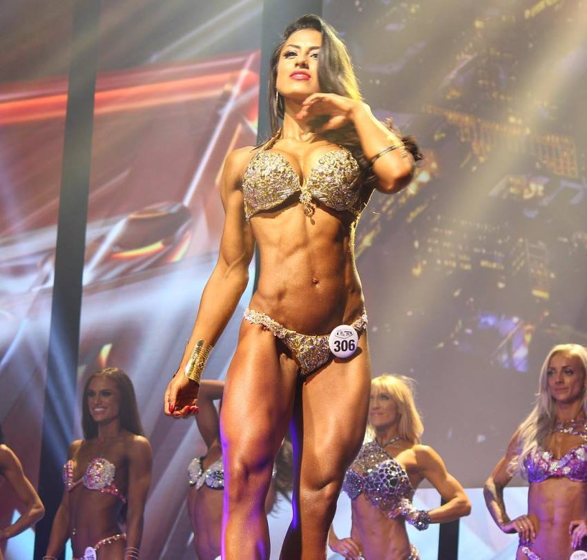 Cristina Silva standing on the WBFF stage in a bikini, looking fit and awesome