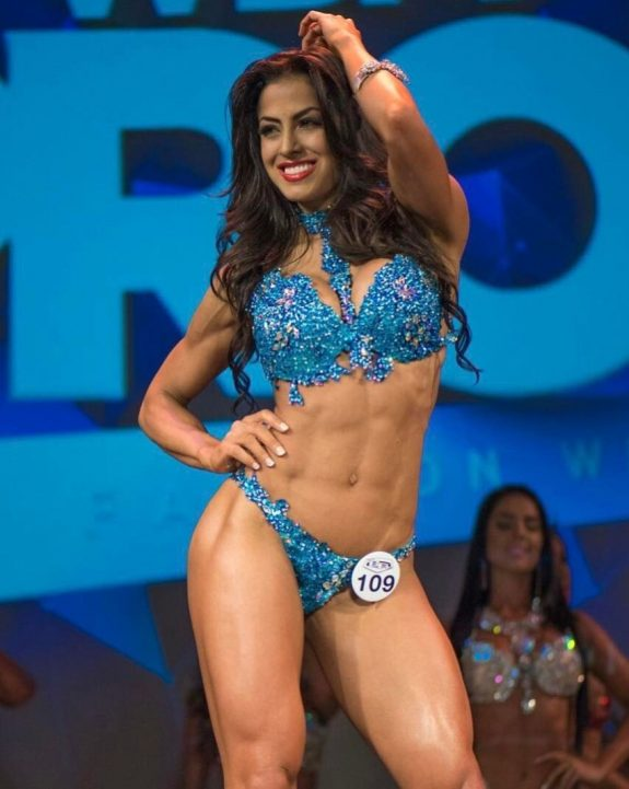 Cristina Silva posing on the WBFF stage in her blue bikini, flexing her fit abs and legs
