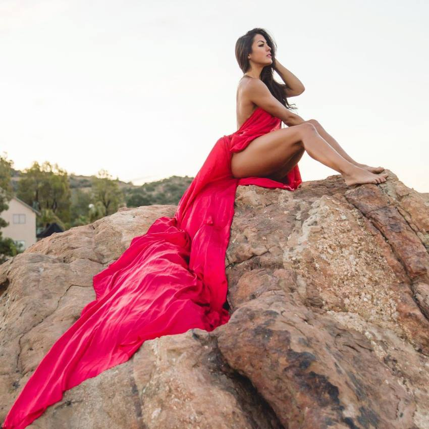 Cristina Silva sitting on the rock in a revealing red silky dress, showcasting her statuesque physique