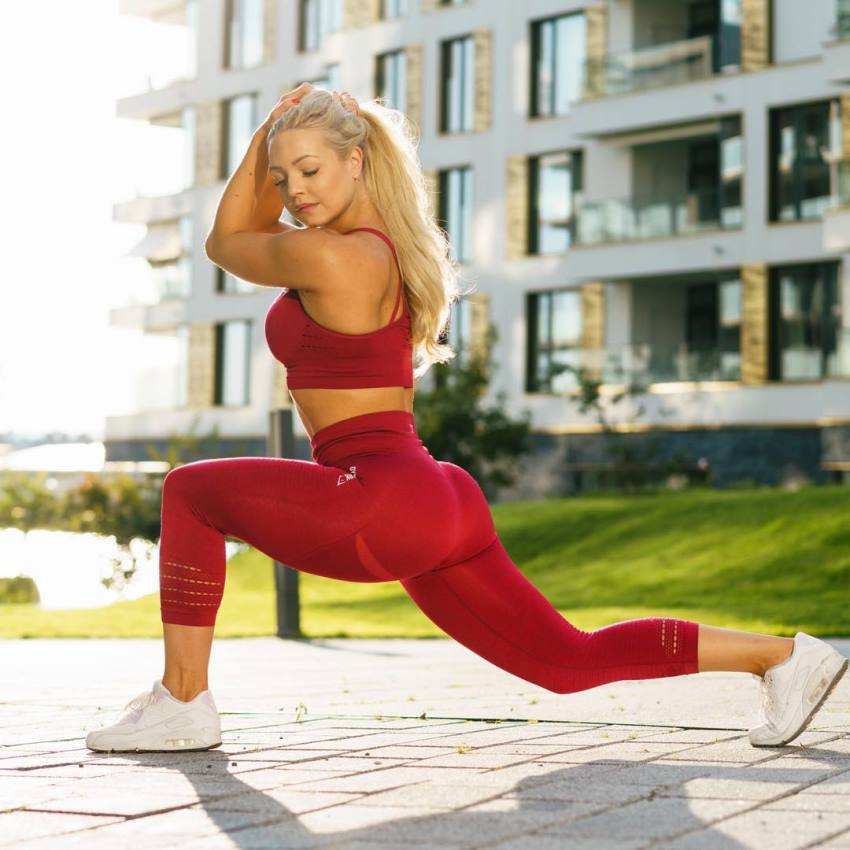 Denice Moberg doing lunges for a photoshoot, wearing tight red leggings