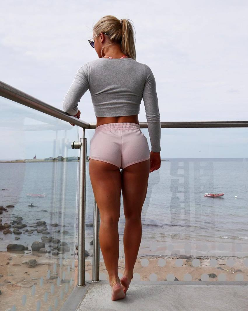 Denice Moberg looking at the sea from the balcony, showing her lean and fit legs and glutes