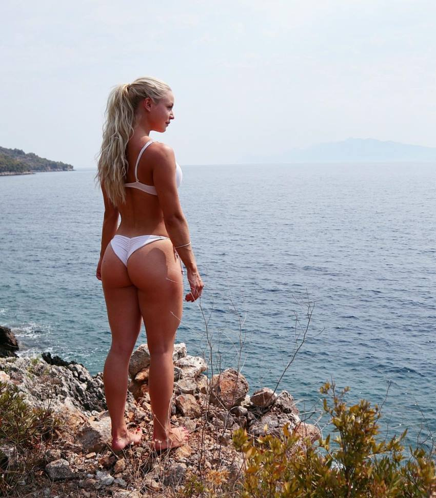 Denice Moberg standing on the rocks overlooking the sea, her legs, back, and glutes looking amazing