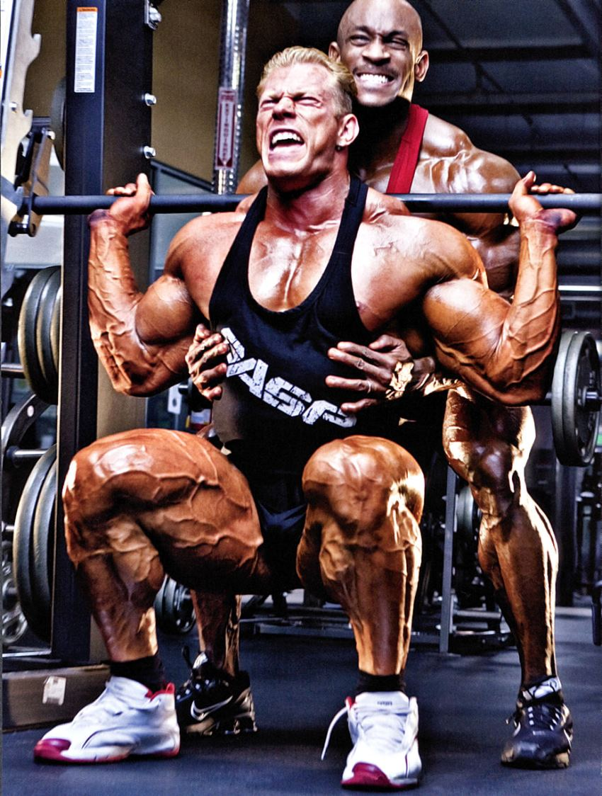 Dennis Wolf doing squats with a pained expression on his face, and a spotter behind him