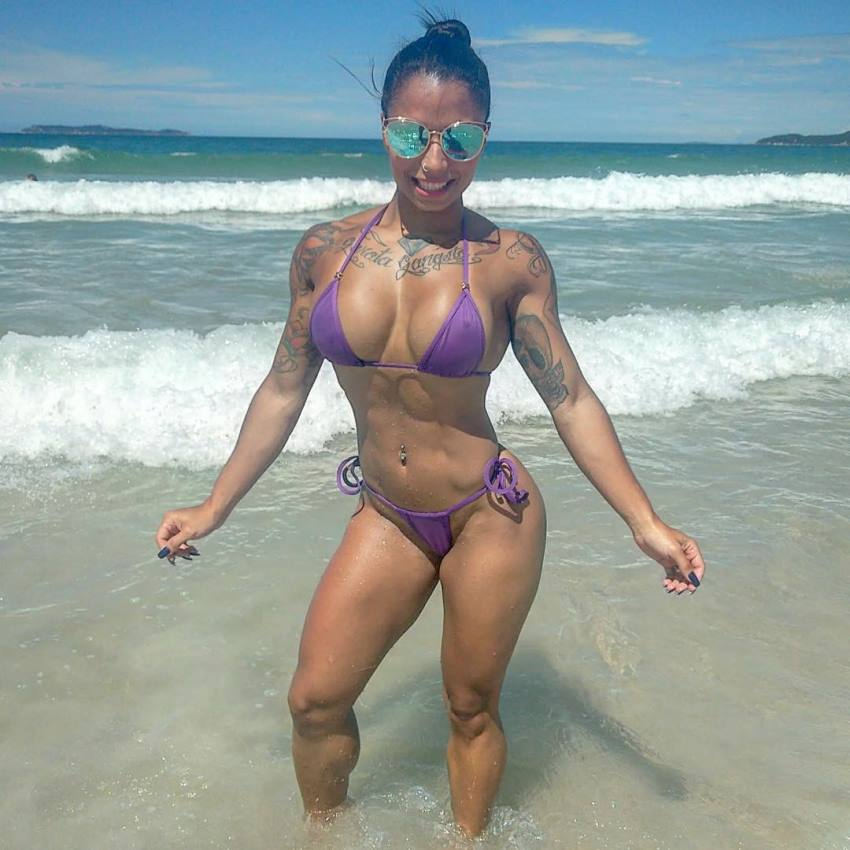 Elah Bittencourt standing on the beach and posing for the camera showing her ripped physique