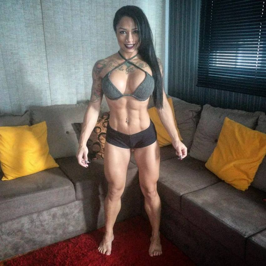 Elah Bittencourt standing in the room showing her flexed abs and legs