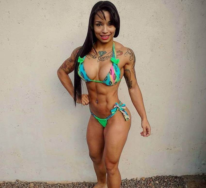 Elah Bittencourt posing in a bikini, looking ripped and stage ready