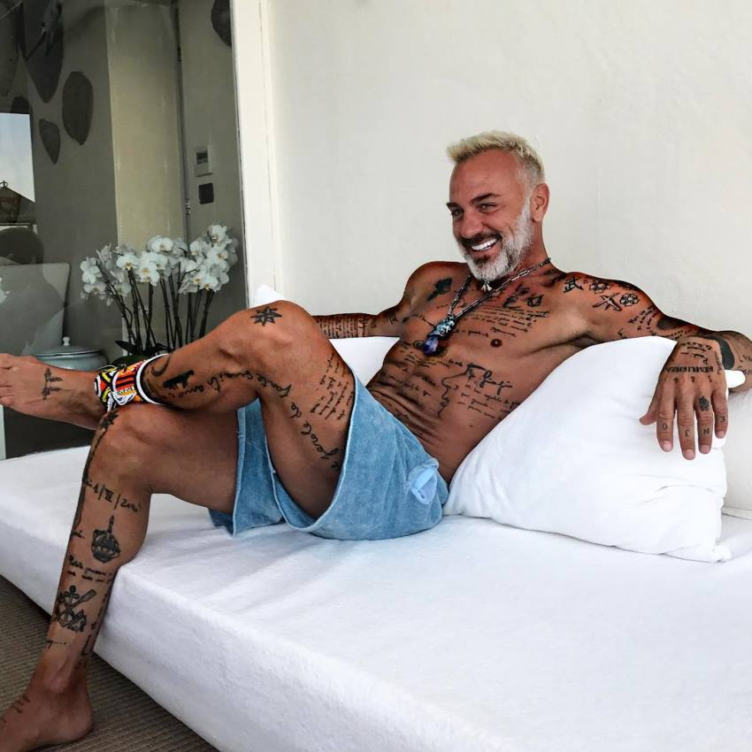 Gianluca Vacchi sitting down on a sofa, smiling, looking lean and happy