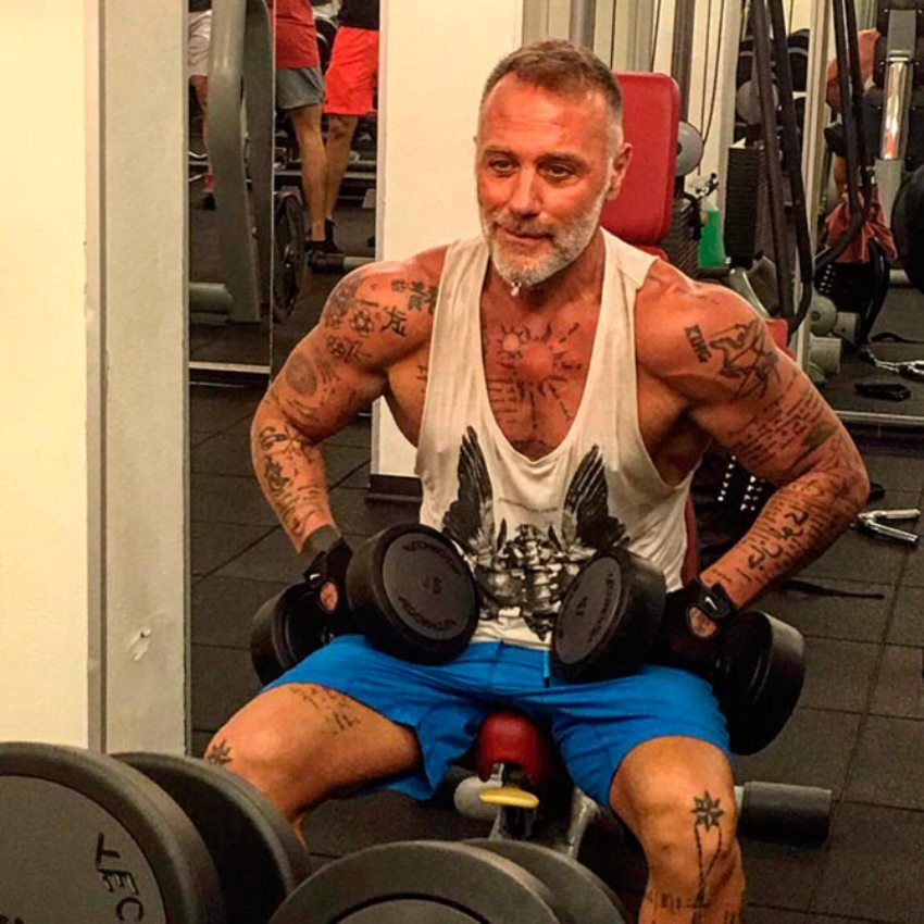 Gianluca Vacchi sitting on a bench in the gym, preparing to do an exercise with dumbbells