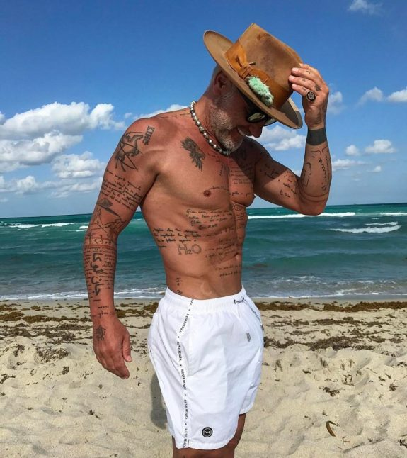 Gianluca Vacchi stainding on the beach with a hat on, looking fit