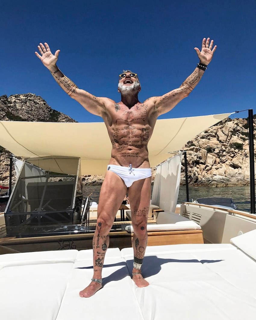 Gianluca Vacchi with his arms spread wide in the air, looking lean and healthy