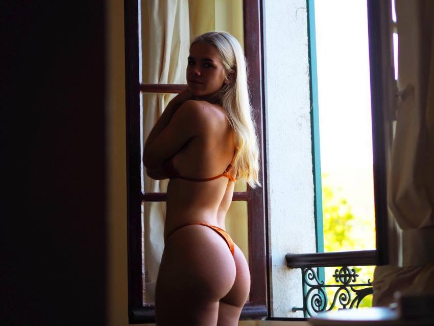 Grace Beverley standing by a window in a shadow, her glutes looking awesome