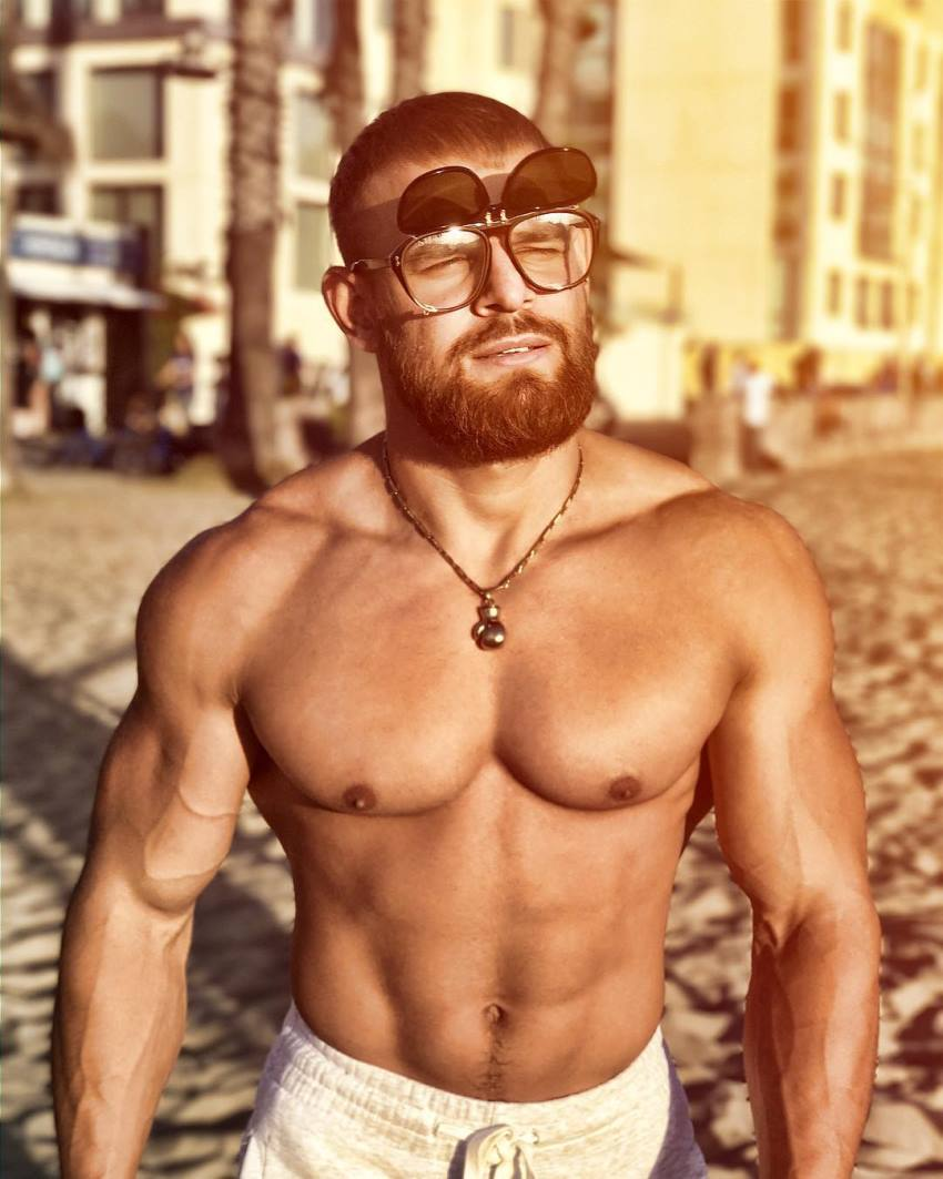Islam Badurgov walking down the beach shirtless with glasses on, looking fit