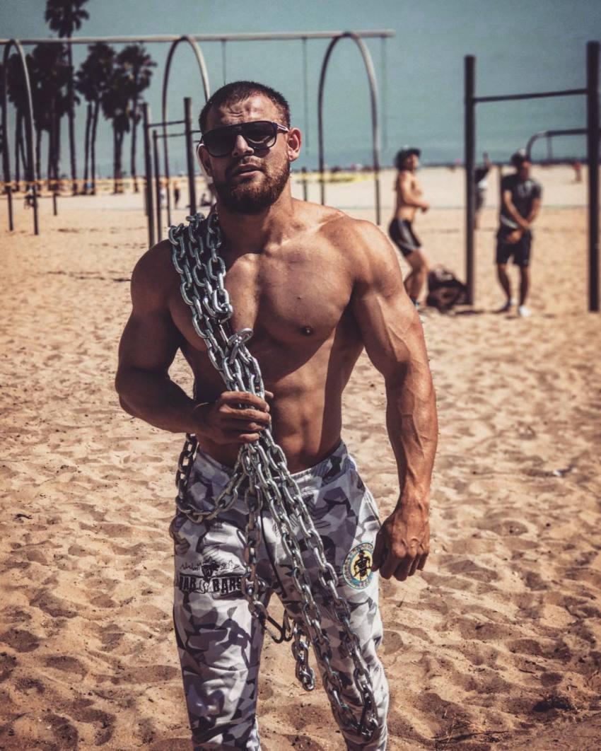 Islam Badurgov shirtless on the beach, having chains on his body