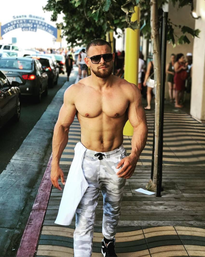 Islam Badurgov walking shirtless on the street, looking lean and aesthetic