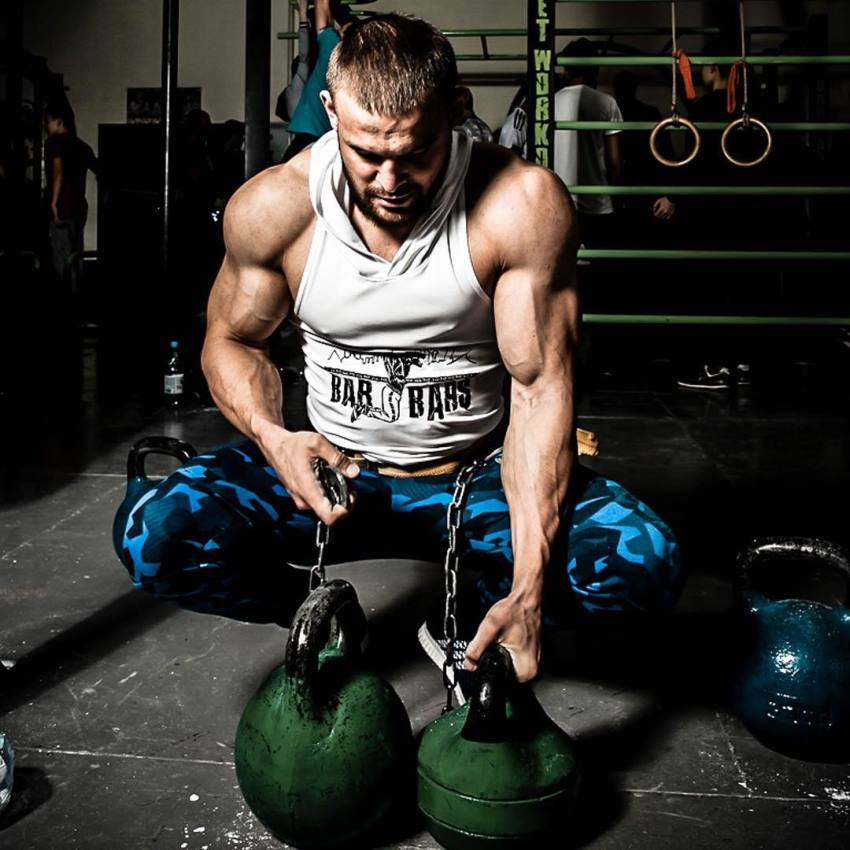 Islam Badurgov holding kettlebels on the floor, wearing a white tank top, looking muscular and ripped