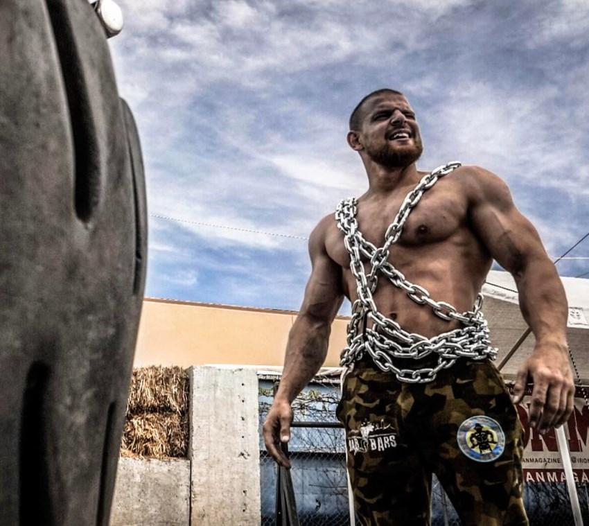 Islam Badurgov standing outdoors with chains around his shirtless body