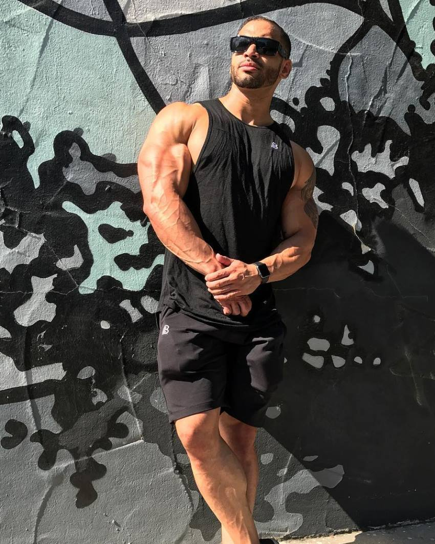 Jamie LeRoyce leaning against the wall in his black tank top, shorts, and sunglasses, his arms looking muscular and ripped