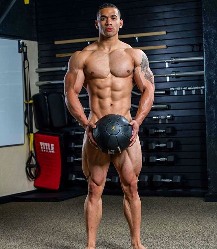 Jamie LeRoyce standing naked, covering his intimate area with medicine ball, looking lean and muscular