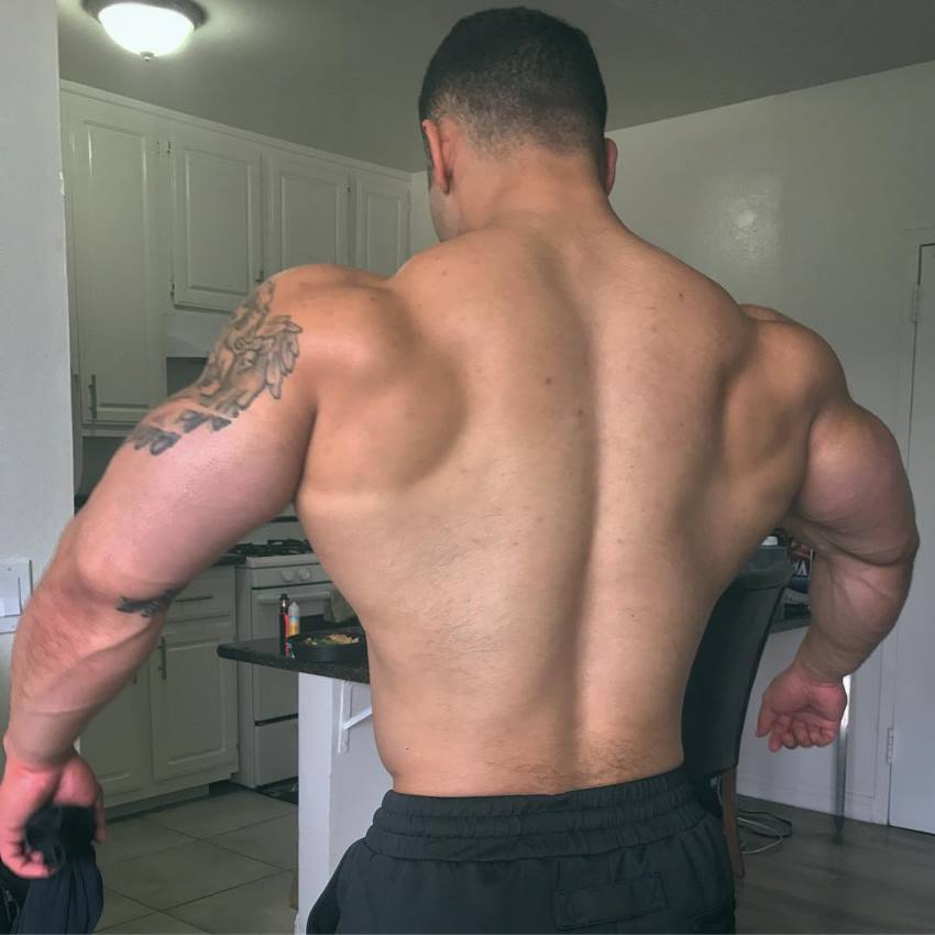 Jamie LeRoyce flaring his arms and lats out, showing his muscular back