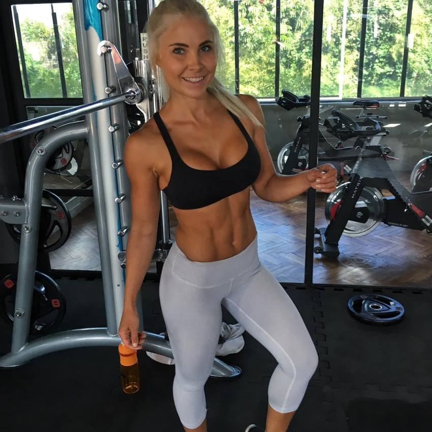 Jaz Correll standing in the gym an smiling at the camera, looking fit and ripped