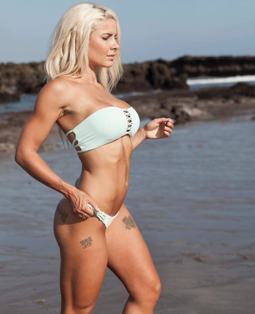Side shot of Jaz Correll standing on the beach, looking fit and aesthetic