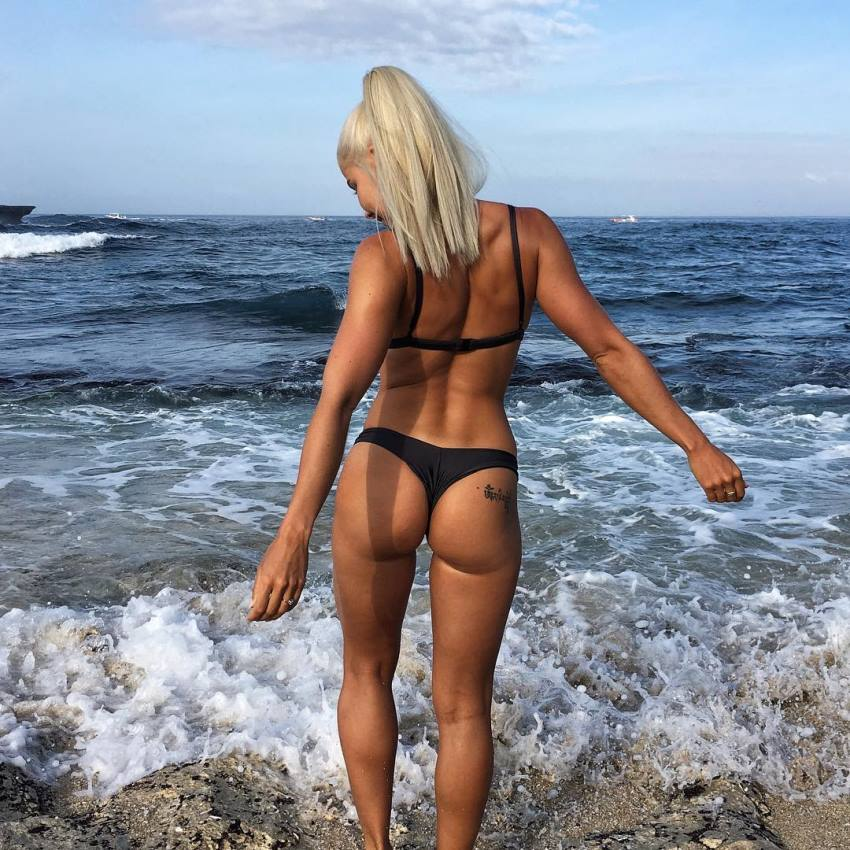 Jaz Correll standing on the shore of the beach, showing her glutes and legs to the camera