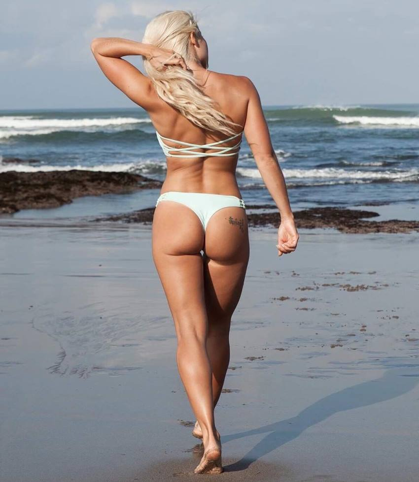 Jaz Correll walking on the beach with her back turned to the camera, her glutes and legs looking amazing