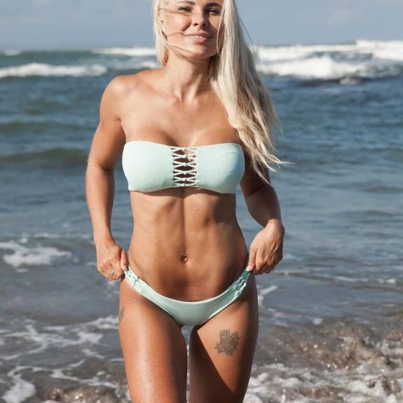 Jaz Correll standing on the beach, smiling and showing her fit physique